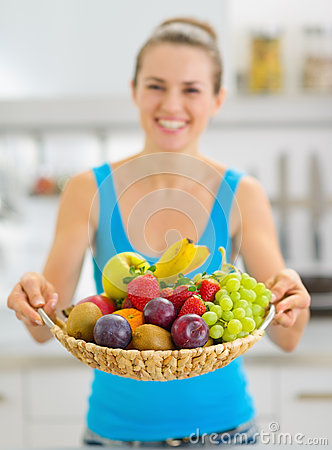 Closeup on plate of fruits giving by smiling woman