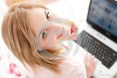 Closeup portrait of beautiful gentle sweet young woman blue eyes girl in bed with laptop and apple looking up