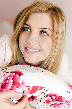 Closeup portrait of blue eyes beautiful happy smiling charming young blond woman lying on bed holding pillow and looking up