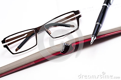 Closeup of reading black glasses on the book with pen