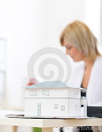Closeup on scale model of house and architect