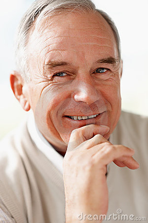 Closeup of a senior man with hand on chin smiling