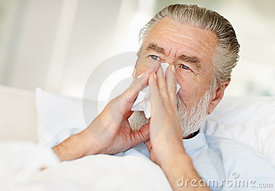 Closeup of a sick senior man blowing his nose