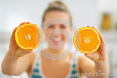 Closeup on slices of orange in hand of young woman
