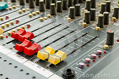 Closeup on sliders of sound mixing console in audio recording