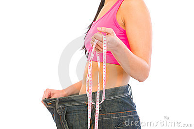 Closeup on slim female in oversized jeans