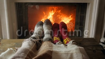 Closeup slow motion video of couple in love in warm socks lying under blanket at living room with burning fireplace. Closeup slow motion footage of couple in stock footage