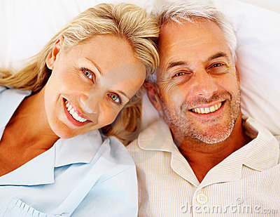Closeup of a smiling senior couple lying on bed