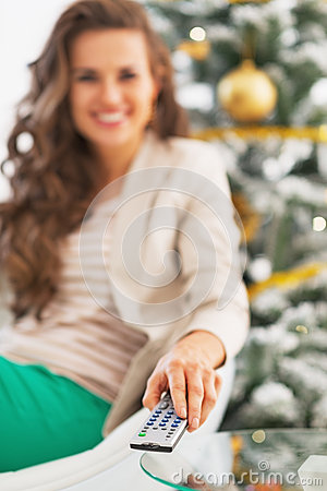 Closeup on smiling woman watching tv in front of christmas tree