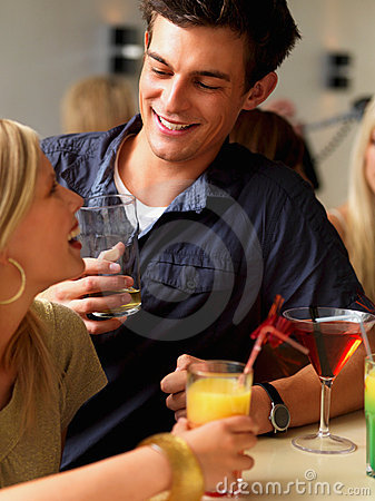 Closeup of a smiling young couple holding drinks