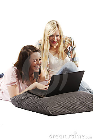 Closeup of smiling young friends using laptop