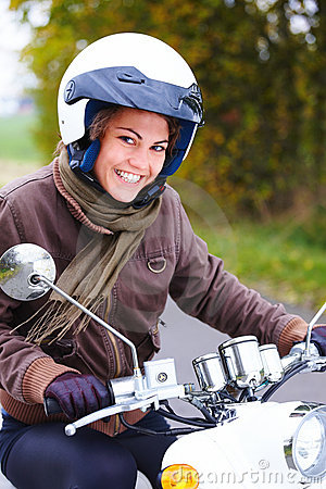 Closeup of a smiling young woman riding moped
