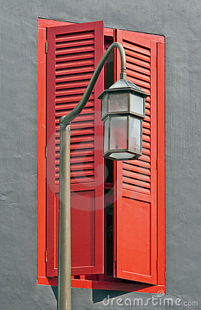 Closeup of streetlamp and red shuttered window