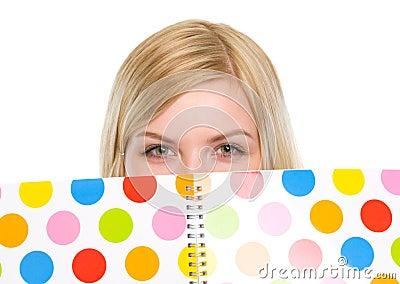 Closeup on student girl hiding behind notebook