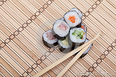 Closeup sushi and chopsticks on bamboo mat
