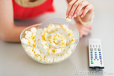 Closeup on teenager girl eating popcorn and watching tv