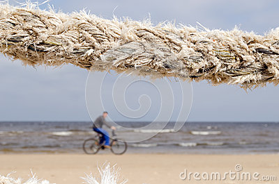 Closeup thick rope and cyclist go sea coast beach