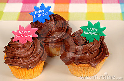 Closeup of three chocolate frosted cupcakes with
