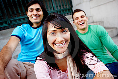 Closeup of three friends sitting together on steps