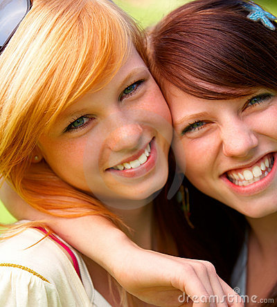 Closeup of two happy pretty teenagers embracing