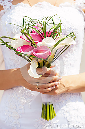 Closeup view of bride holding bouquet of callas