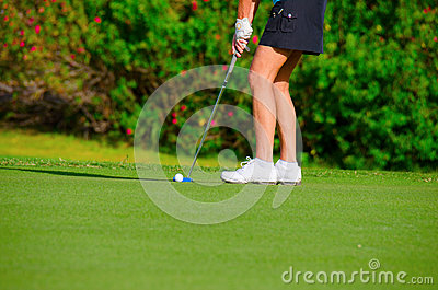Closeup of woman golfer putting on the green