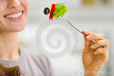 Closeup on woman holding fork with salad