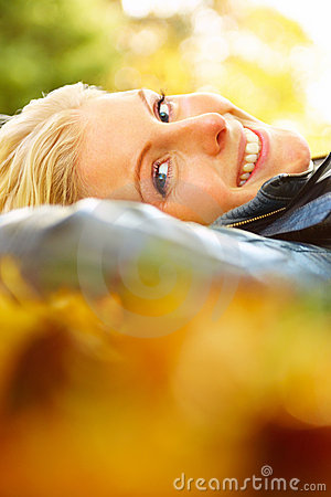 Closeup of a woman lying on leaves looking at you