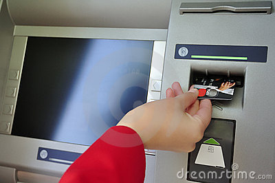 Closeup of woman s hand inserting card into ATM