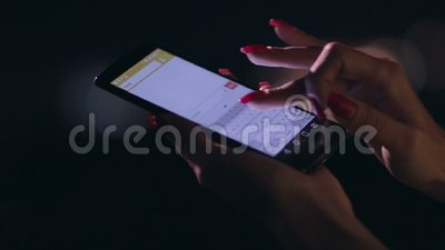 Closeup woman's hand texting on cellphone at night stock footage