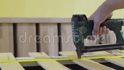 Closeup of worker holds board with stapler  Action  Worker uses stapler to  bond tape with wood boards in furniture