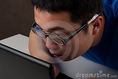 Closeup of young asian man working on laptop