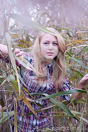 Closeup of young beautiful blond woman in reed