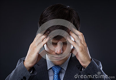 Closeup of young business man with headache