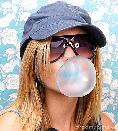 Closeup of a young girl blowing bubble gum