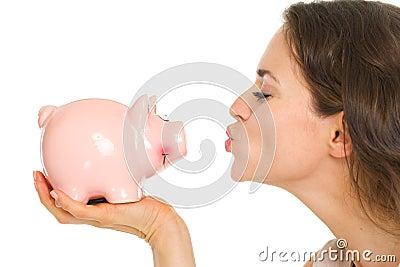 Closeup on young woman kissing piggy bank