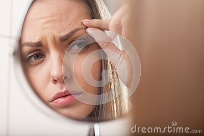 Closeup of young woman looking into mirror.