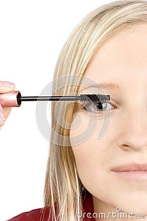 Closeup of young woman s face putting mascara