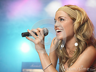 Closeup Of Young Woman Singing Into Microphone