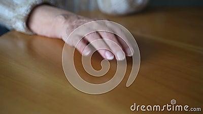 Closeupen av gamla woman's räcker knackning som är nervös på tabellen lager videofilmer