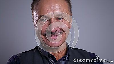 Closeupstående av den lyckliga höga caucasian manliga framsidan som glatt ler och ser rak på kameran lager videofilmer