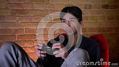 Closeupstående av den unga koreanska mannen som spelar videopp cames genom att använda konsolen som inomhus sitter i bönapåsen stock video