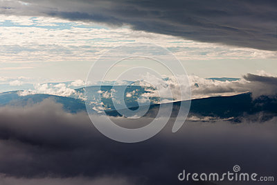 Clouds billow between hill and mountain landscape