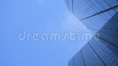 Clouds Business Corpoate Building. This is time lapse footage of clouds flying in the sky and being reflected on a big glass building that represents corporate stock video footage
