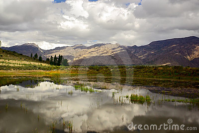 Clouds reflect in clear mountain lake in africa