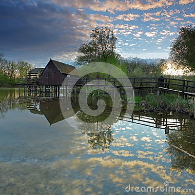 Clouds reflection in water with watermill