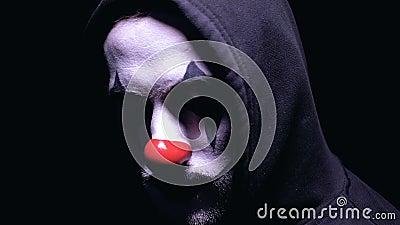 Clown avec le sourire fou se tournant vers la caméra sur le fond foncé, cauchemar clips vidéos