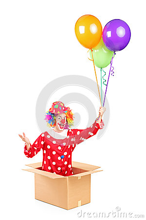 A clown in a cardboard box holding balloons