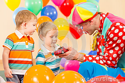 Clown making present kid boy on birthday party