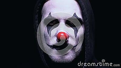 Clown mauvais souriant à la caméra sur le fond foncé, fou dangereux dans le masque banque de vidéos